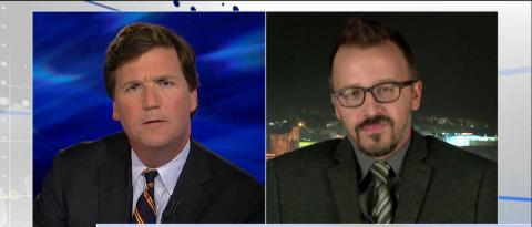A Drexel University professor who said he wanted to 'vomit' after an airline passenger gave up a first-class seat for a soldier engaged in a heated debate tonight with Tucker Carlson.